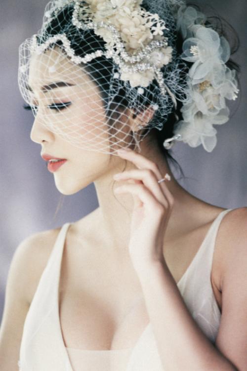 Mạng che mặt dáng ngắn được đính thêm đá và hoa bản to giúp tân nương thêm lộng lẫy trong ngày trọng đại.