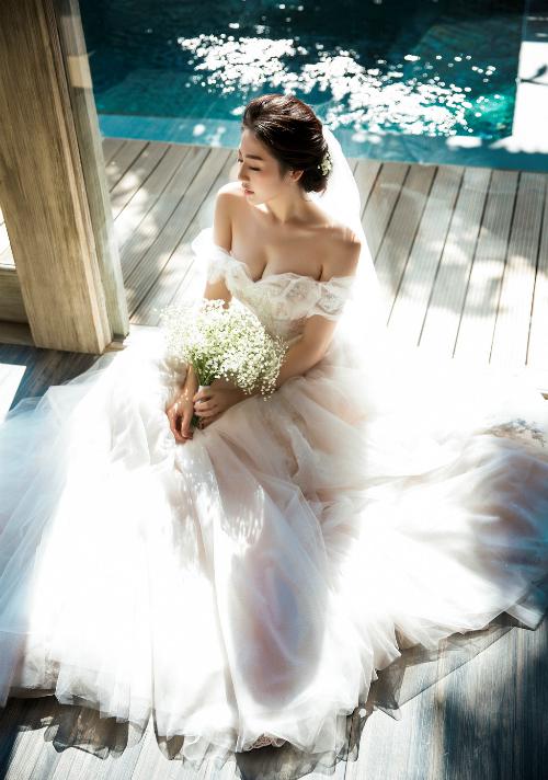 Dù từng hóa thân thành cô dâu nhiều lần khi trình diễn áo cưới nhưng khoảnh khắc trở thành cô dâu thực sự, Tú Anh vẫn khiến mọi người xiêu lòng bởi vẻ đẹp mong manh và nét duyên e ấp. Cô chọn một chiếc váy cưới trễ vai dáng bồng xòe không cầu kỳ nhưng nổi bật. Ảnh: Lê Thiện Viễn.