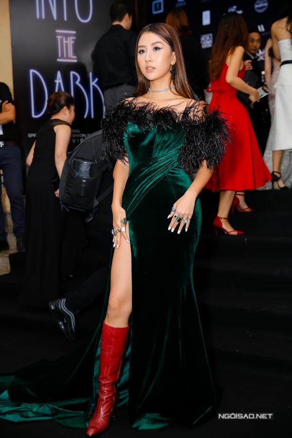 Quỳnh Anh bất chấp tiết trời mùa hè khi chọn váy nhung đính lông vũ để phối cùng bốt da đỏ.