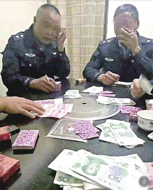 Những tờ tiền mệnh giá lớn được đặt trên bàn trong khi nhóm nhân viên quản lý đô thị chơi bài. Ảnh: The Paper.