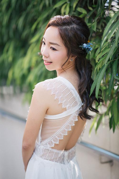 Trong ngày trọng đại, cô dâu không làm tóc quá cầu kỳ mà chỉuốn xoăn nhẹ, buộc nửa đầu và điểm xuyết thêm một nhành hoa màu xanh baby.