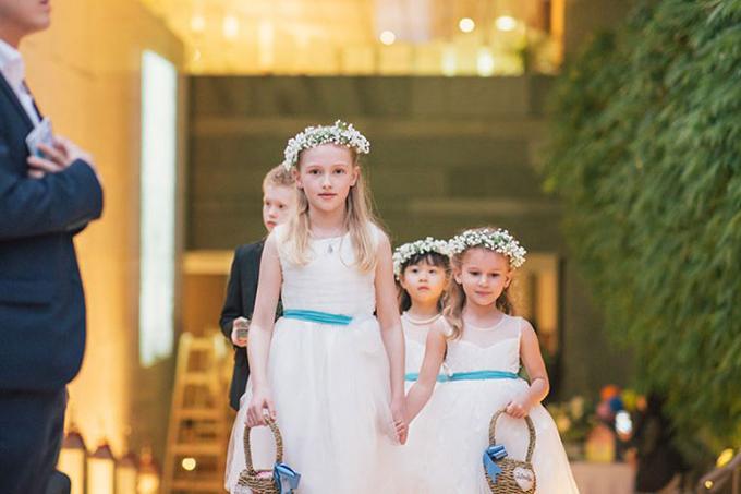 Các cô bé phù dâu nhí đáng yêu trong những chiếc váy với nơ xanh và giỏ hoa có ruy băng cùng màu.