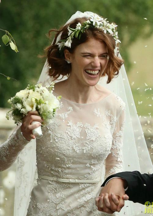 Mái tóc bob ngắn của Leslie được uốn lọn mềm mại. Vòng hoa đội đầu và hoa cầm tay của cô dâu đồng điệu với hoa văn trên thân váy, càng làm tôn lên nét tinh khôi ngày cưới.