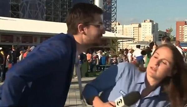 Nữ phóng viên người Brazil nhanh nhẹn nghiêng người, tránh bị CĐV Nga hôn. Ảnh: SporTV.