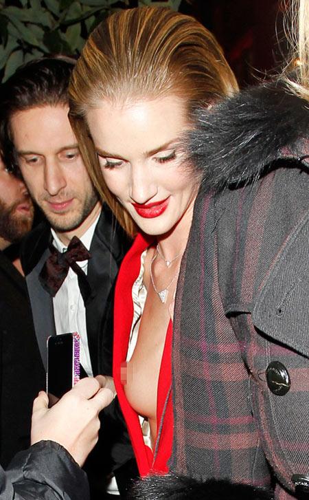 Gây ấn tượng trên thảm đỏ British Fashion Awards tối 3/12 bởi vẻ sexy, thanh lịch nhưng khi rời lễ trao giải, người đẹp Transformers 3 Rosie Huntington-Whiteley không may lộ cả bầu ngực trước mặt nhiều fan.