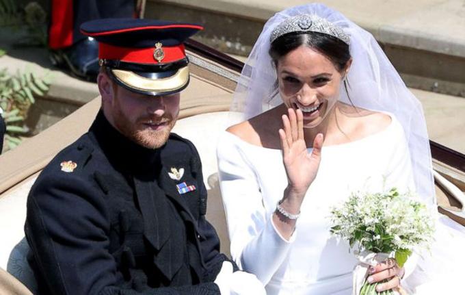 Vợ chồng Harry - Meghan ngồi trên xe ngựa vẫy tay chào công chúng sau khi kết thúc hôn lễ ở nhà nguyện St George hôm 19/5. Ảnh: Reuters.