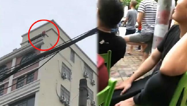 Đám đông vừa đứng vừa ngồi bên đường để chờ xem cảnh nhảy lầu. Ảnh cắt từ video.