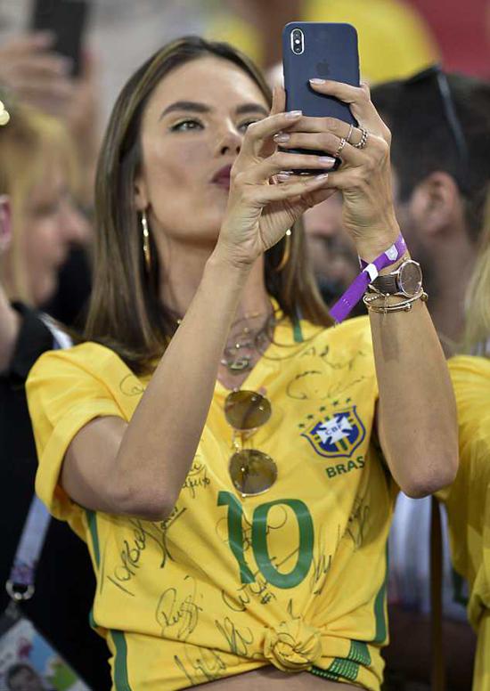 Alessandra Ambrosio tới Nga cổ vũ cho đội Brazil quê hương của cô. Siêu mẫu 37 tuổi xuất hiện nổi bật trên khán đài tối thứ tư trong màu áo vàng xanh in đầy chữ ký của các ngôi sao đội bóng xứ sở samba.