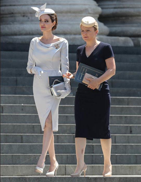 Tại sự kiện này, Angelina váy bút chì trang nhã thương hiệu Ralph & Russo, kết hợp hài hòa với chiếc mũ thắt nơ kiểu cách, găng tay và ví đồng màu.