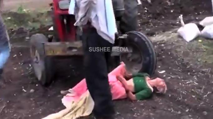 Cụ bà bất lực khi bị con trai lôi xềnh xệch trên mặt đất ra trước chiếc máy kéo. Ảnh: Sushee Media.