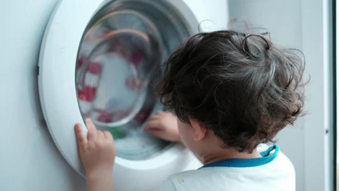 Trẻ em dễ bị mắc kẹt khi chui vào máy giặt và không thể ra ngoài nếu không có người giúp. Ảnh minh họa.