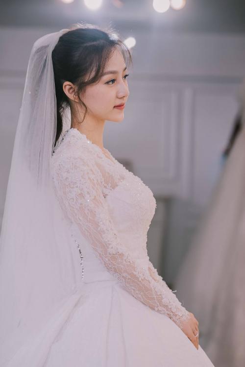 Chiếc váy trắng ren dài tay mang đậm phong cách vintage cổ điển, tạo vẻ yêu kiều cho cô dâu.