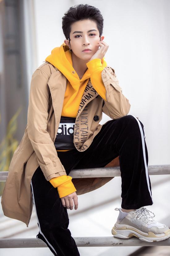 Giữa trời mùa hè, casĩ không ngại diệnáo hoodie vàng nghệ, bên ngoài khoác áo măngtô màu nâu nhạt với điểm nhấn họa tiết nơi cổ áo.
