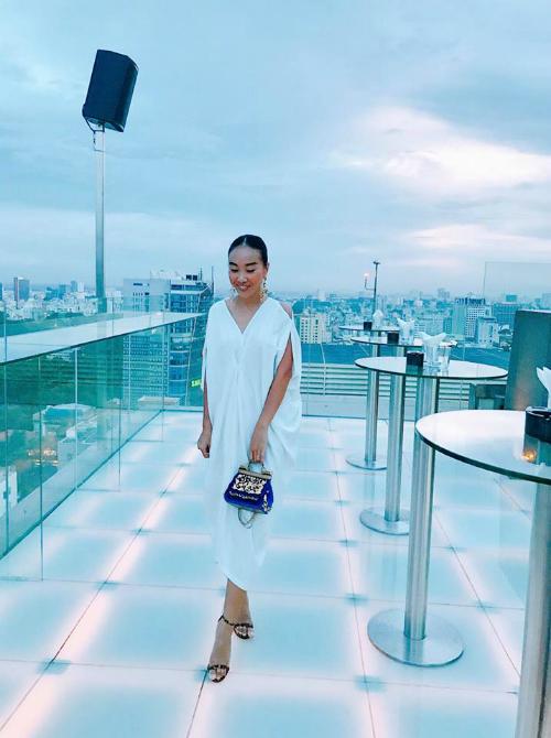 Đoan Trang diện nguyên cây đồ màu trắng, tạo dáng phong cách khi ở Bangkok, Thái Lan.