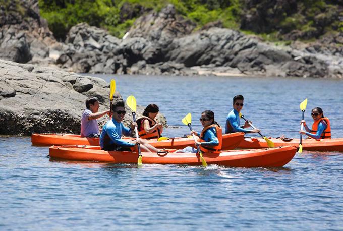 Hai cặp vợ chồng cùng bố mẹ thích thú chèo thuyền ngắm cảnh thiên nhiên, sông nước Nha Trang.
