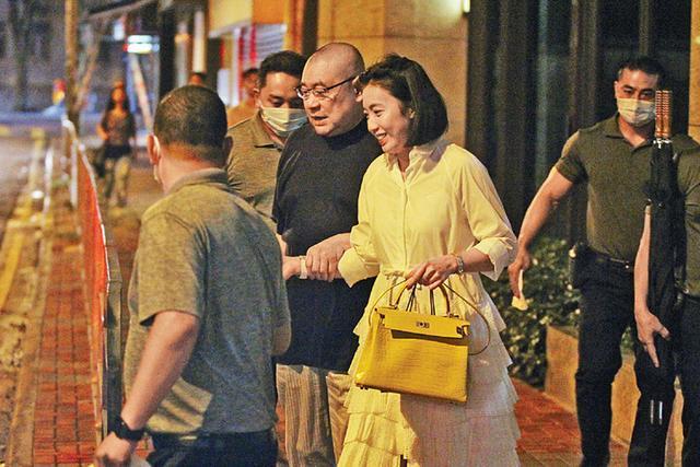 Tỷ phú Lưu Loan Hùng được vợ dìu khi ra xe hơi.