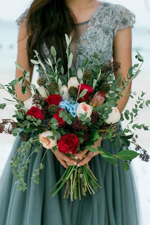 Cận cảnh bó hoa cưới kết từ hoa hồng, cẩm tú cầu của cô dâu. Chiếc váy cưới của cô dâu cũng mang tông xanh nước biển thay vì váy cưới trắng truyền thống.