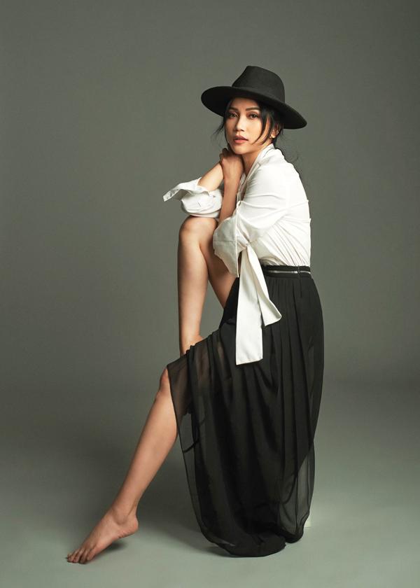Sĩ Thanh phối màu trắng đen cuốn hút với mũ fedora, sơ mi lụa và chân váy phối vải voan xuyên thấu.