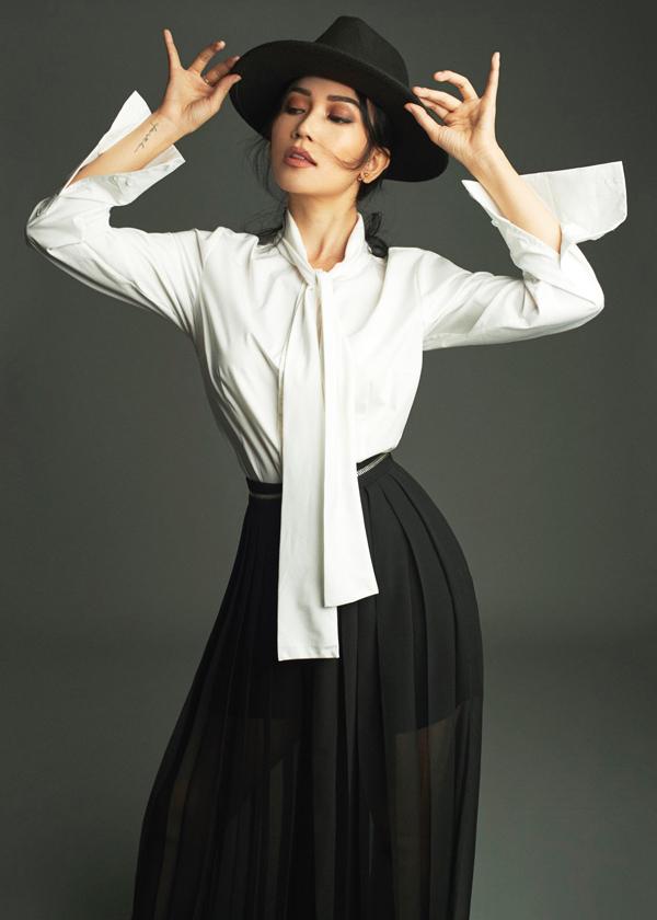 Áo sơ mi trang trí dải nơ dài được phối hợp hài hòa cùng chân váy midi theo phong cách cổ điển.