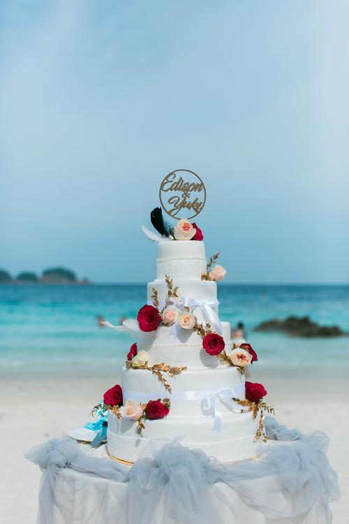 Chiếc bánh kem 5 tầngđược tô điểm bởi tên của hai vợ chồng, những bông hoa hồng tươi xinh xắn, lông vũ, ruy băng xanh và trắng.