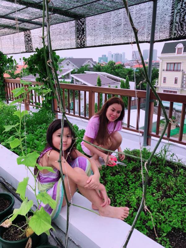 Con gái hoa hậu thích xem mẹ làm vườn và thỉnh thoảng giúp mẹ bắt sâu, tưới rau.