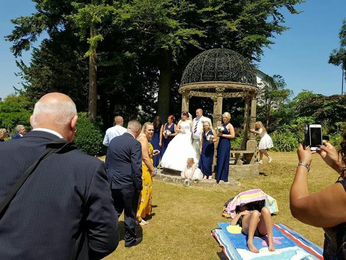 Cô gái vô tư tắm nắng dù xung quanh cô dâu, chú rể và rất nhiều khách mời đang chụp ảnh. Ảnh: The Sun.