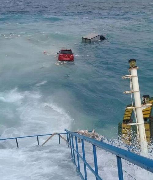 Xe ôtô và xe tải bị cuốn ra biển. Ảnh: Twitter.