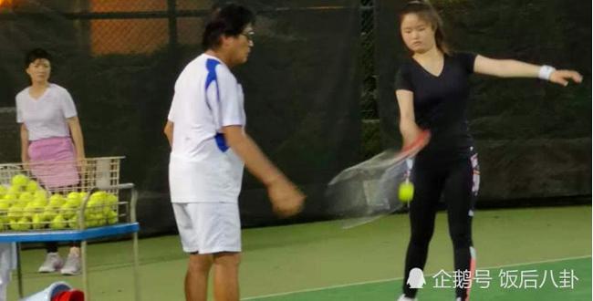 Con gái của Thiếu Hà (áo đen) được bố dượng chỉ dạy các động tác của môn tennis.