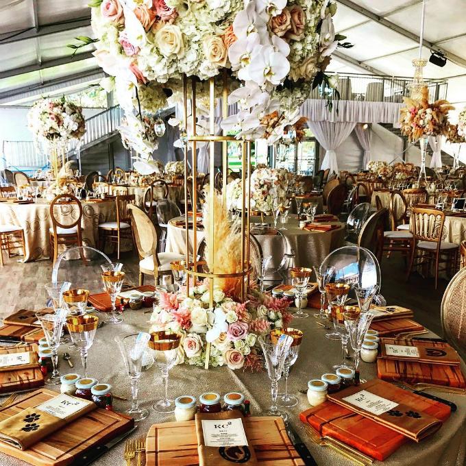 Bàn tiệc được trang trí bởi trụ hoa hồng tươi, lan hồ điệp, cẩm tú cầu và lông vũ.