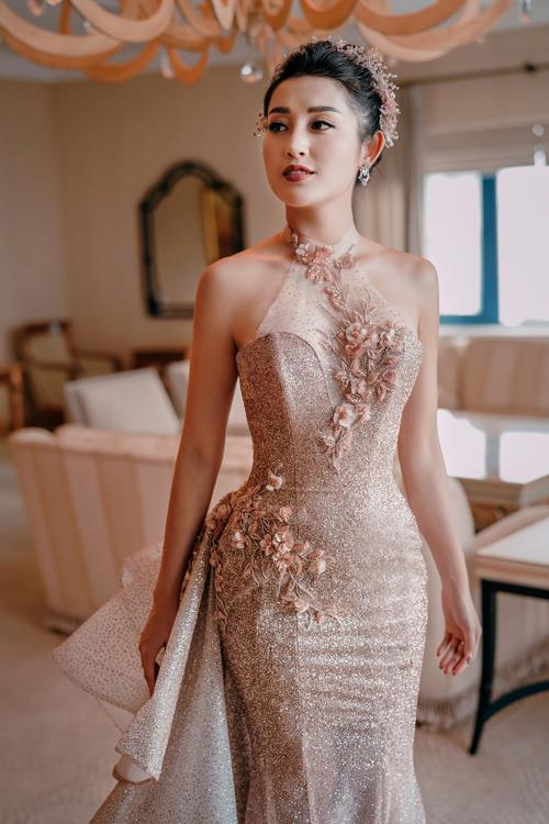 1. Váy cưới dáng Sheath: Huyền My diện váy lấp lánh với thiết kế cổ hai trong mộtgồm cổ yếm và cổ cúp ngực. Họa tiết hoa được đính từ cổ đến ngực áo và ngang hông cùng tông nâu đồngsáng với màu váy.
