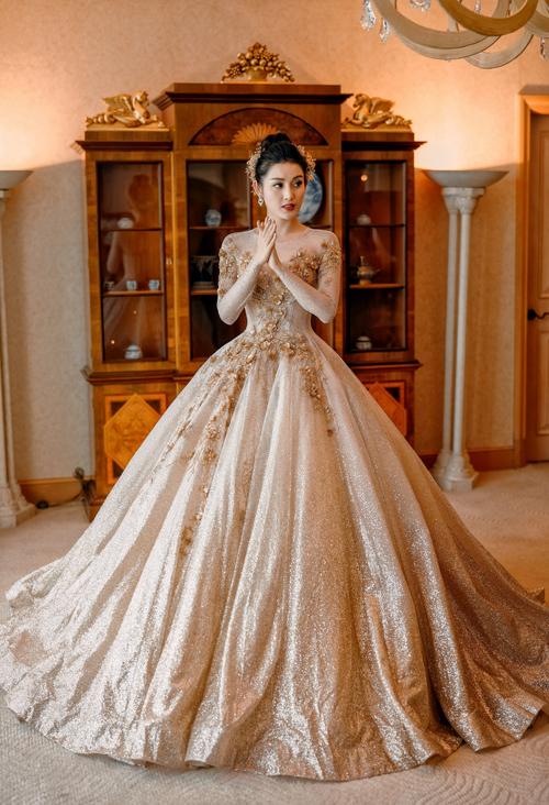 2. Váy cưới xòe bồng công chúa: Bộ đầm ánh kim lộng lẫy hô biến Á hậuHuyền My thành nàng công chúa bước ra từ câu chuyện cổ tích ngày xưa. Bộ váy tiếp tục được nhà thiết kế tạo hình cổ hai trong một để khoe khóe nét đẹp của cô dâu trong ngày cưới.