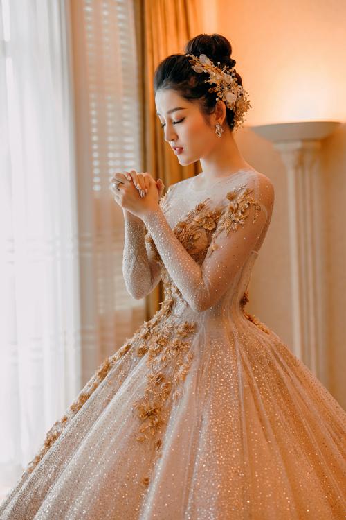 Chiếc váy được đính kim sa thủ công, tỉ mỉ, thích hợp cho các cô dâu yêu thích phong cách sang trọng. Điểm nhấn chính là phần ngực áo và thân váy được đính hoa thêu nổi, tạo nên nét tinh tế và mềm mại cho bộ đầm. Tóc cô dâu được búi cao và cài bờm đá lấp lánh.