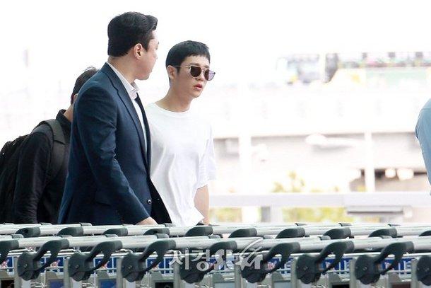 Jung Hae In được trợ lý hộ tống tại sân bay.