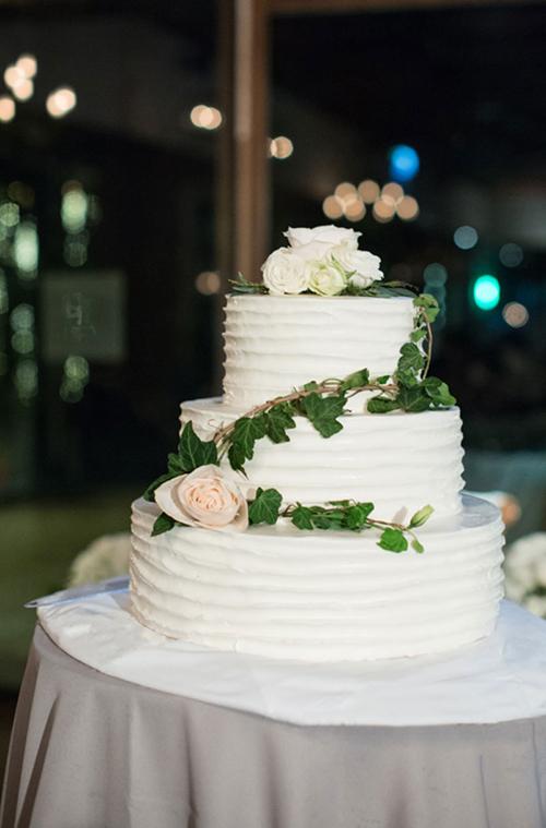 Bánh cưới ba tầng của uyên ương với đường vân lượn sóng được tạo hình bằng nĩa. Thợ làm bánh đã mô phỏng hình ảnh hoa hồng trắng và dây leo giống y như thật để trang trí bánh cưới.