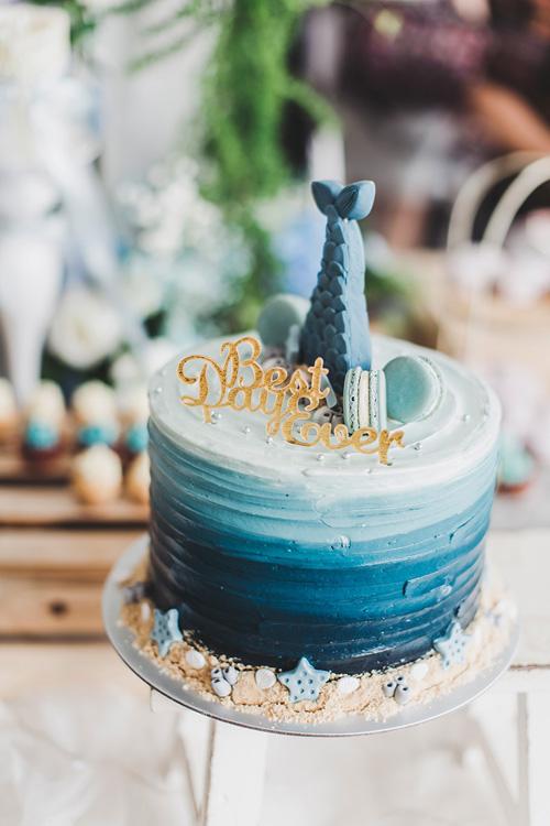 Với yêu cầu củacô dâu, ekip wedding planner đã đặt bánh cưới xanh ombre được trang trí bởiđuôi cá, bánh macaroni, ngôi sao biển,mẩu vụn bánh mô phỏng hình hạt cát và tất cả đều ăn được.
