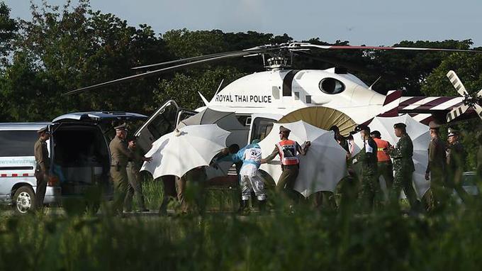 Cảnh sát Thái Lan dùng ô để che chắn khi một người vừa được đưa ra khỏi hang được đưa xuống trực thăng bằng cáng.Ảnh:AFP.