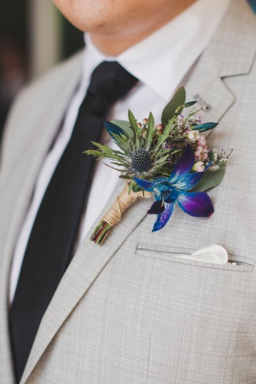 Chú rể diện hoa cài áo mang sắc xanh của hoa lan tươi, lá cây và sắc hồng từ hoa thanh liễu.