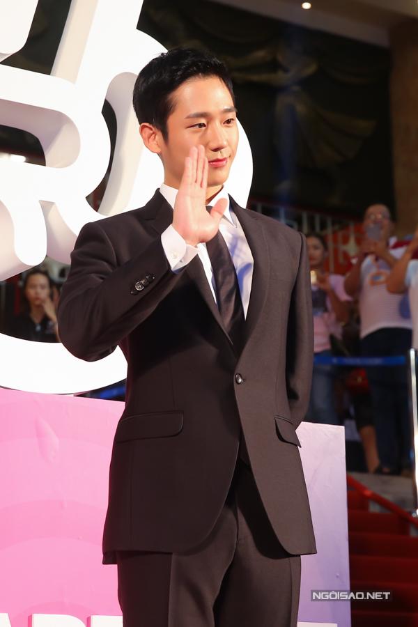 Jung Hae Indiện vest bảnh bao và vẫy tay chào khán giả. Nam diễn viên Hàn Quốc sinh năm 1988, trực thuộc công ty giải trí FNC Entertainment. Anh sở hửu ngoại hình điển trai và bắt đầu khởi nghiệp với một số vai phụ trong: Goblin,Yeah, Thats the way it is; Night light... Tuy nhiên, tên tuổi anh thực sự tạo dấu ấn sau khi đóng cặp với đàn chịSon Ye Jin trong Chị đẹp mua cơm ngon cho tôi.