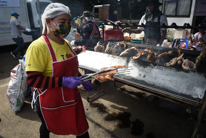 Các đầu bếp nướng gà để phục vụbữa ăn của tình nguyện viên và nhân viên cứu hộ bên ngoài hang động. Ảnh: AFP.