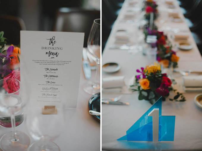 Menu tiệc cưới được tối giản các chi tiết trang trí, các món ăn được viết bằng phông chữ viết tay nổi bật. Các bàn tiệc được đánh số để phân loại. Không gian tiệc ngập tràn sắc đỏ, vàng và tím rực rỡ.