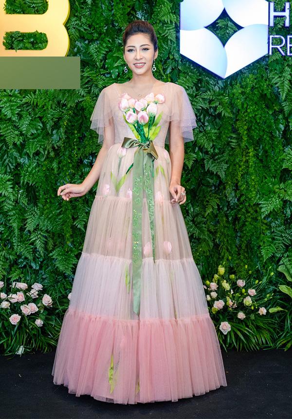 Mẫu đầm hồng nhiều tầng của Hoa hậu Đại dương 2014 Đặng Thu Thảo càng thêm sến khi được nhấn nhá bó hoa sen giả trước ngực.