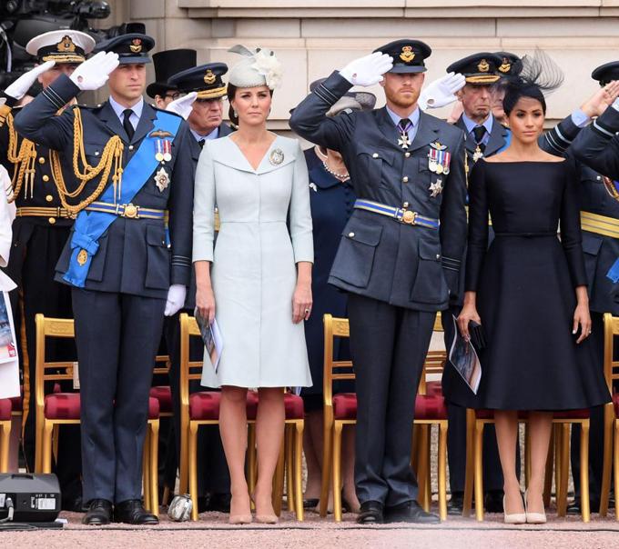 Trong khi hai Hoàng tử mặc quân phục, Kate chọn váy màu xanh nhạt, còn Meghan lại diện màu tím than tương phản.