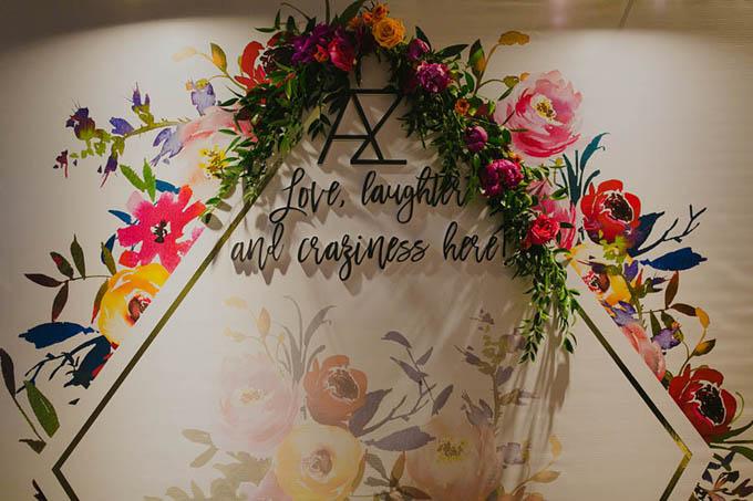 Background chụp hình lãng mạn với những bông hoa sặc sỡ. Cô dâu đã tự tay thiết kế chữ AZ lồng vào nhau, vốn là chữ cái đầu của tên hai vợ chồng. Đồng thời cô còn sắp xếp vị trí chỗ ngồi cho khách mời.
