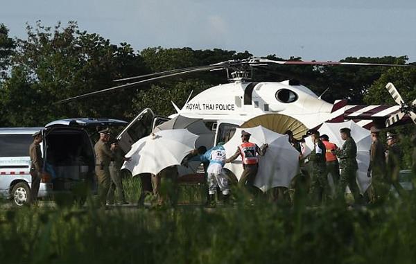 Các nhân viên cứu hộ dùng ô che chắn khi đưa người được giải cứu lên trực thăng. Ảnh: AFP.