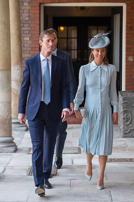 Pippa Middleton cùng chồng đại gia tài chính James Matthews. Pippa chọn váy màu xanh và giày, mũ, túi cùng màu. Cô hiện mang thai 6 tháng.