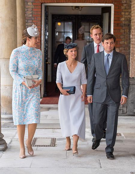 Khi vào trong nhà nguyện, Lucy đi cùng cha mẹ đỡ đầu khác của Louis là vợ chồng Robert Carter (bên phải) và Harry Aubrey-Fletcher (đằng sau).