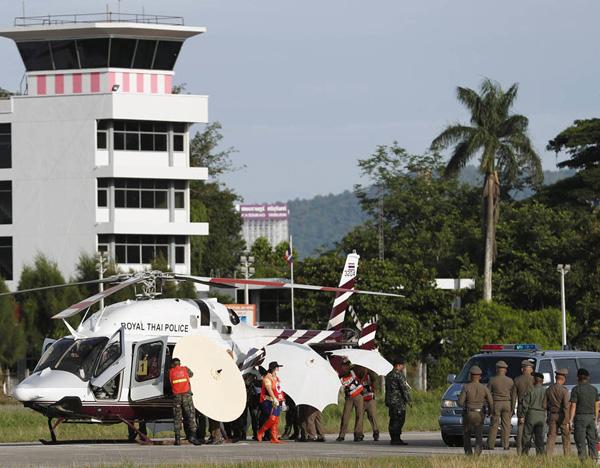 Các nhân viên cứu hộ dùng ô che chắn khi đưa người được giải cứu lên trực thăng