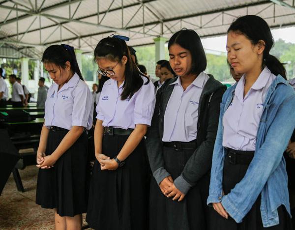 Bạn cùng trường của một số cầu thủ trong đội bóng Wild Boars cầu nguyện cho cuộc giải cứu thành công trước giờ học.