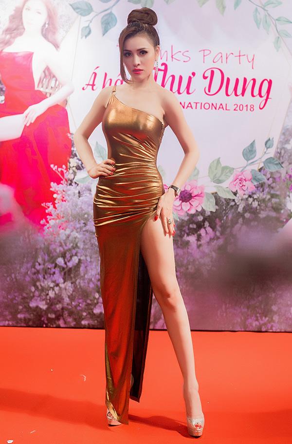 Á hậu khoe dáng sexy trong bộ váy lệch vai màu đồng, xẻ gần tới hông.
