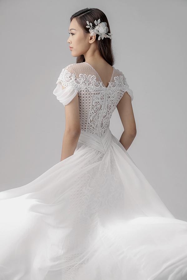 Váy cho cô dâu được tạo điểm nhấn bằng họa tiết đính kết thủ công với hình hoa lá, những cánh chim đang bay lượn trên bầu trời.